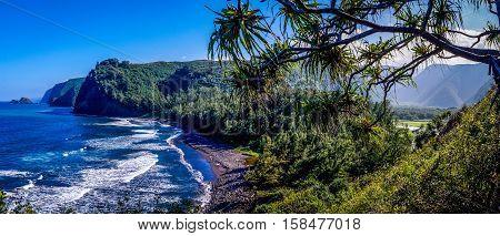 Panorama overlooking Pololu Valley, Big Island Hawaii, USA shows waves clashing against a beautiful volcanic black sand beach