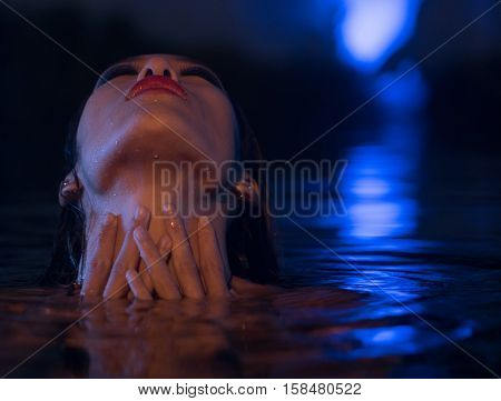 Closeup face of sexy Asian woman with wet hair standing in the swimming pool with head lying down on the water and hands on her neck during summer evening over blue lights background
