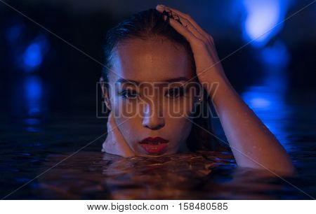 Closeup face of sexy Asian woman with wet hair standing in the swimming pool and looking into the camera during summer evening over blue lights background