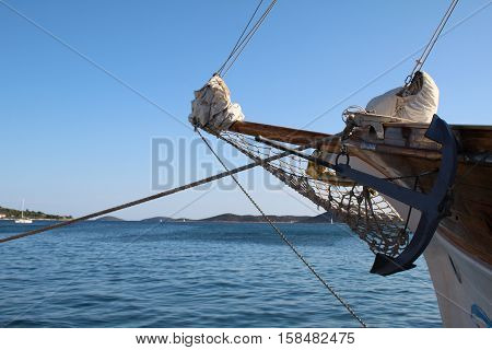 Fragments of a pirate ship / Anchor of a pirate ship on a background of blue sky.