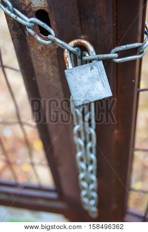 padlock with chain on a closed gate