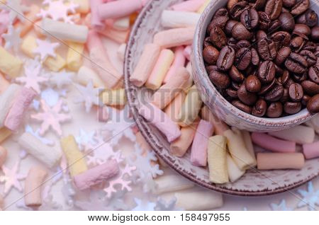 Cup of coffee beans with pink girlish marshmallow and sparkling snowflakes shallow depth of field