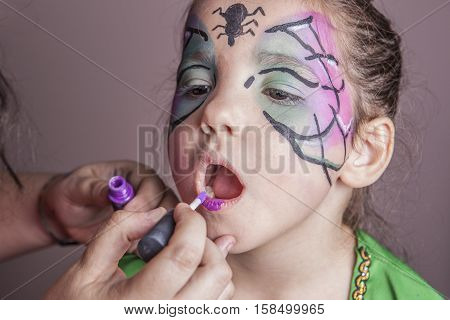 Make-up artist working with a little girl before halloween party. She is applying purple lip gloss