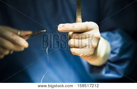surgeon's hands holding a needle and thread and a needle holder