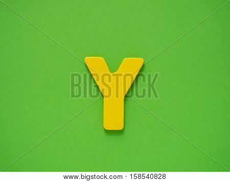 Capital letter Y. Yellow letter Y from wood on green background.