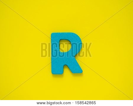 Capital letter R. Blue letter R from wood on Yellow background.
