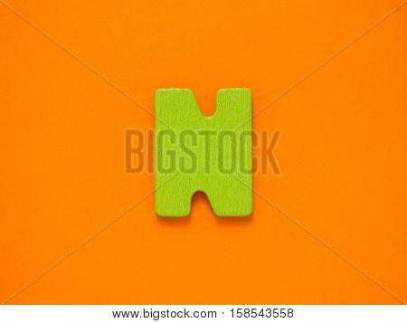 Capital letter N. Green letter N from wood on orange background.