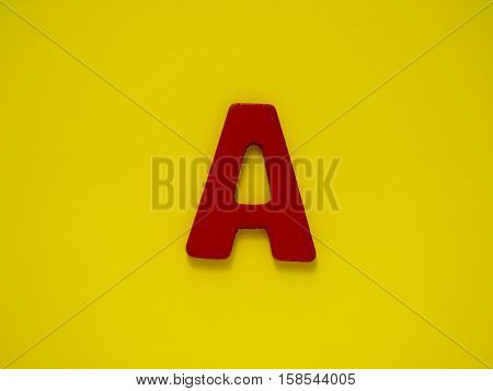 Capital letter A. Red letter A from wood on yellow background. Alphabet vowel.