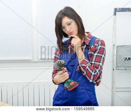 pretty young brunette woman holding cordless drill