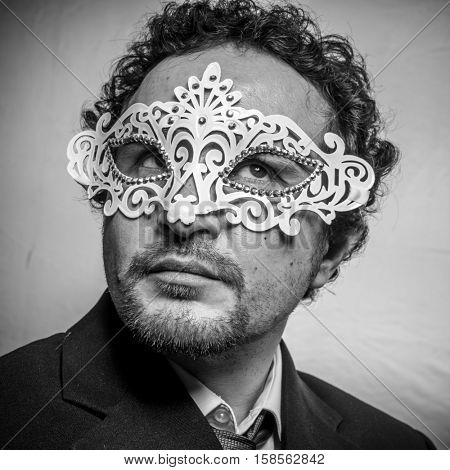 Sensual and mysterious businessman with white venetian mask