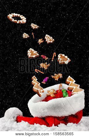Christmas gingerbread cookies and candies fly away of a Santa Claus hat to the cosmos.Greeting cars for Christmas and New year