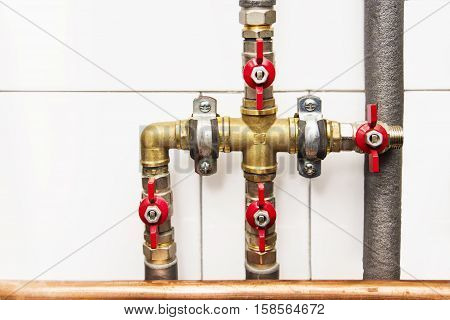 Copper valves and pipes on a white wall