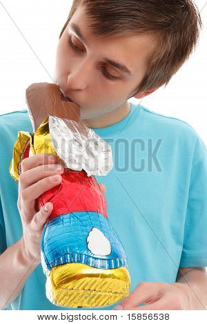 Boy Biting Ear Of Chocolate Rabbit