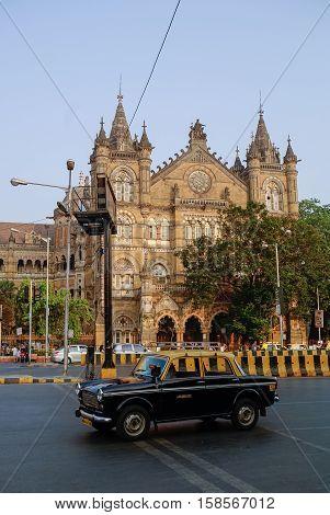 Mumbai, India - January 1, 2012: Famous Mumbai yellow-black taxi car and at background Chhatrapati Shivaji Terminus (CST) is a UNESCO World Heritage Site and an historic railway station in Mumbai