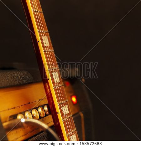 Combo amplifier for electric guitar with guitar neck on the black background. Shallow depth of field low key close up. Focus on neck.