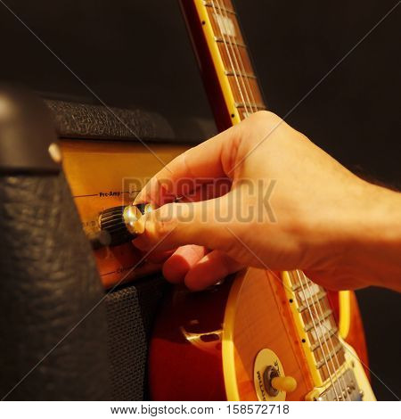 Hand adjusts amplifier for guitar with electric guitar on the black background. Shallow depth of field low key close up.