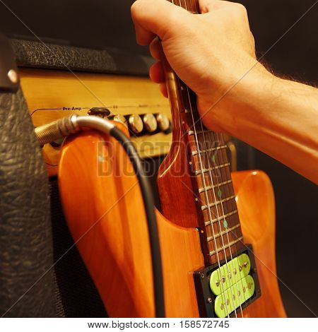 Hand puts electric guitar to combo amplifier on the black background. Shallow depth of field low key close up.