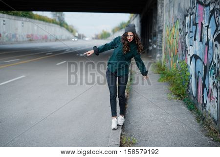 A beautiful young girl with curly hair and glasses view, tiptoe into the street on the curb near a wall painted graffiti. She wears the cap of a fall and enjoy life.