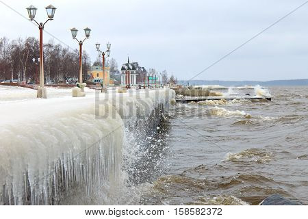 Winter storm on the lake and ice-covered city embankment. Onegalake, Petrozavodsk, Russia