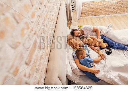 Our friendly family. Top view of mother, father and their children taking nap in bed in morning with cat beside them