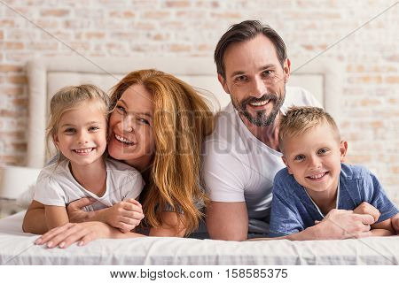 Spending quality time together. Happy mature parents playing with their smiling kids while hugging tightly