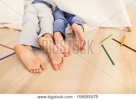 Spending time at home. Close up of feet of sleeping little boy and girl while lying on floor in bedroom