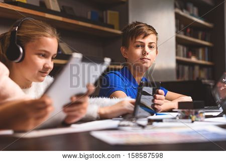 Boy is sitting in library and looking at camera with interest. He is smiling. Girl is studying with tablet
