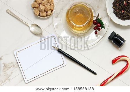 Over head flat lay view of golden herbal tea, loose tea leaves, raw sugar cubes, vintage spoon, vintage pen and ink, blank notecard and candy cane.  Open space for copy.