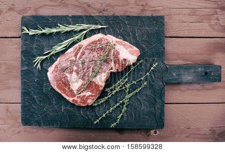 Raw rib-eye steak on black cutting board, toned image