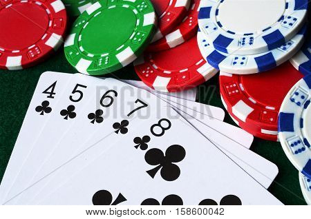 A top view image of poker chips and playing cards.