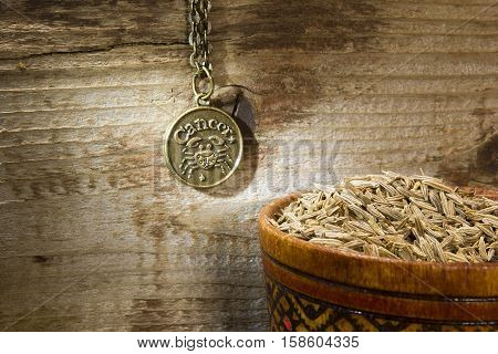 Cumin seeds in a wooden bowl and a sign of the zodiac
