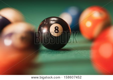 Pool ball with number 8 over green background.