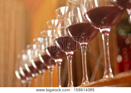 Row of glasses with red wine on bar counter, closeup