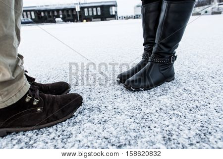Male and Female casual boots standing on asphalt covered gritty snowY surface. Rough snowy surface. Textplace. Cold Winter. Side view