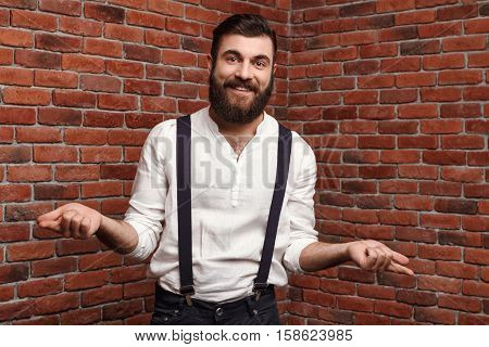 Young handsome man in suit with suspenders smiling gesturing over brick background. Copy space.