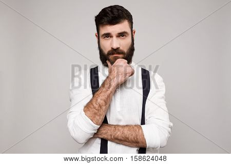 Young handsome man in suit with suspenders thinking posing over white background. Copy space.