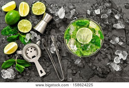 Cocktail juice with lime mint and ice. Bar drink accessories on black table background. Alcoholic and nonalcoholic cold drinks. Selective focus