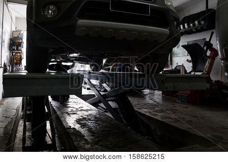 Silhouette Of Mechanics Repairing Car At Small Workshop Garage