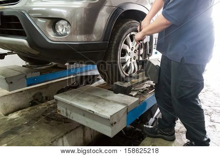 Mechanic Fixing Car Aligner Onto Car Wheel