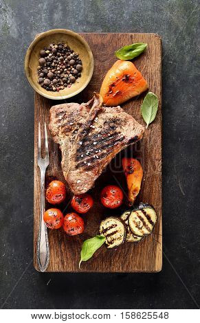 grilled beef steak on a cutting board on a black background