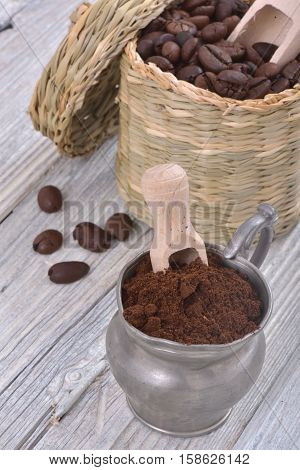 Vintage metal cup with ground coffee on a white wood with coffee beans in the background