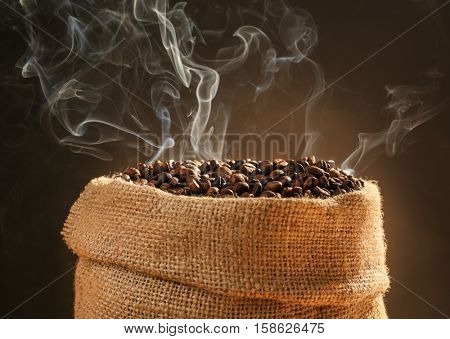 Sack with roasted coffee beans on dark background, close up view