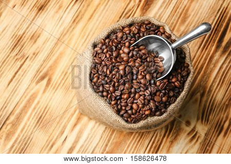Sack with coffee beans and scoop on wooden background