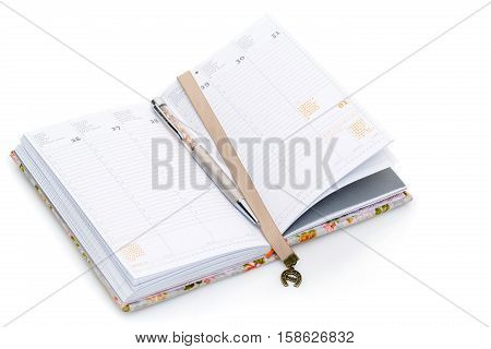 Notebook opened on first of January. Bookmark ribbon with horseshoe. Isolated on white. Copy space.