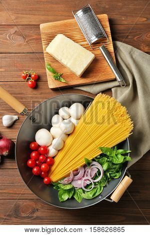 Pan with ingredients for tasty pasta, grater, napkin and kitchen board on wooden table, top view