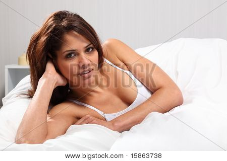 Young woman propped up in bed