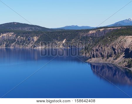 The steep banks of Crater Lake reflect in the deep blue waters on a sunny summer morning.