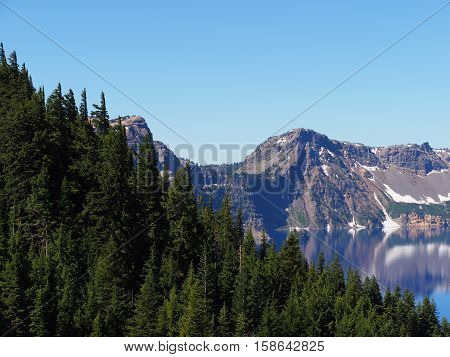 Seen through the trees the rugged rim of Crater Lake reflects in the deep blue water.