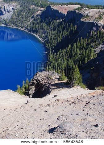 A drop off with a view of a cove in Crater Lake on a sunny summer morning.