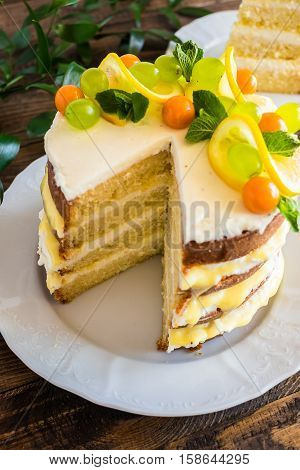 Biscuit layered cake with cream cheese and lemon curd decorated with fresh mint leaves, physalis, lemon slices and green grapes on a plate, selective focus